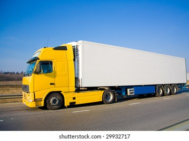 Yellow white blank truck on a country road