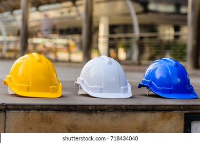 Yellow, white and blue hard safety helmet hat for safety project of foreman and engineer or worker, on the concrete floor.