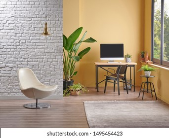 Yellow and white brick wall background in the room, chair easel painting style, vase of plant and working computer on the wooden table.