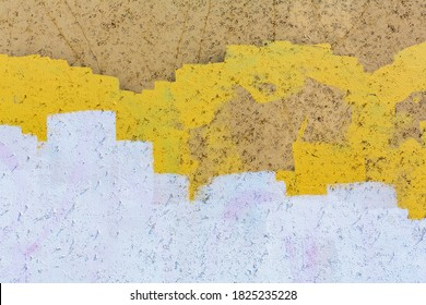 Yellow, white and brown paint covering graffiti on building wall