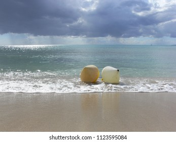 yellow and white buoys on the beach in front of clear water and a vivid sky with rainclouds and sun at Mallorca, Spain