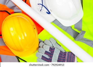 Yellow and white hard safety hats with protective gloves and glasses laying on a pile of hi vis vests