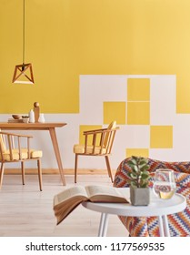 Yellow and white interior room decoration with sofa armchair and frame.