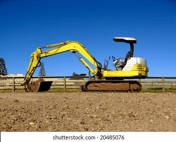 A yellow and white mini digger excavator.  Space for Copy.
