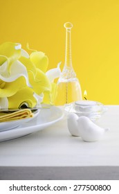 Yellow and white theme wedding table place setting with heart shape plates on white shabby chic style wood table.