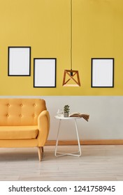 Yellow and white wall room background, yellow sofa white white table and wooden lamp, several frame on the wall.