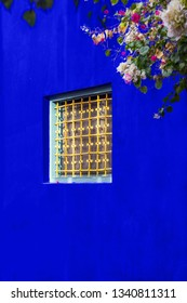 Yellow window grate in the blue painted wall with bunch of flower hanging from one corner