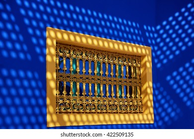 The yellow window with a grid on the background of two blue walls with sun reflections