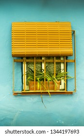 Yellow window on  blue wall