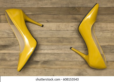 yellow women  shoes  heels on wooden background top view