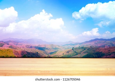 Yellow wood table top with blue sky view on the high mountain. Sunshine day. Mock up for display or montage of product. Can be use for banner, advertising, online media, business. Copy space.