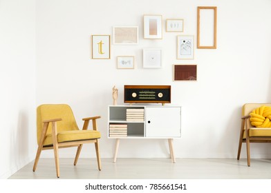 Yellow wooden armchair next to white cupboard with radio against a wall with mockup of poster in warm living room interior