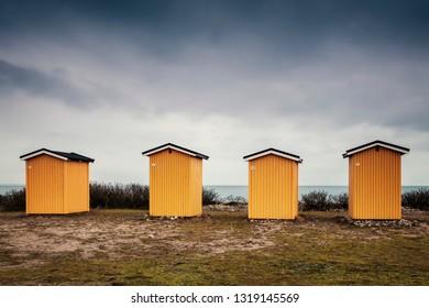 Yellow wooden beach huts. Viken, Sweden.