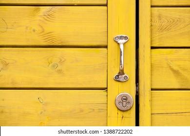 Yellow wooden door with a shiny handle. Metal door handle. Wood texture. Yellow tree. Concept Minimalism. Closed door.