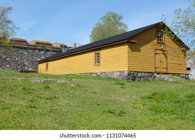 Yellow wooden hut with a black roof and stone foundations on a grassy patch on Suomenlinna island