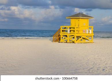 A yellow wooden lifeguard hut on an empty morning beach