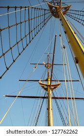 Yellow wooden mast of old sailing boat