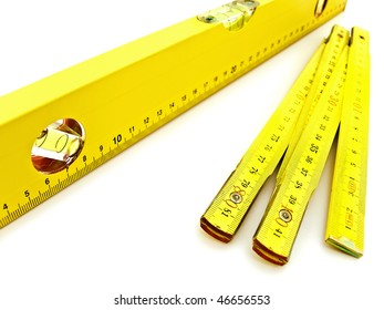 yellow wooden meter and level over the white background