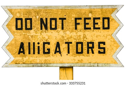 Yellow wooden warning sign with black text. Do not feed Alligators.. Vintage board in an alligator farm in Florida Everglades USA warning visitors not to feed animals, yellow background black type
