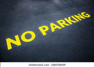 Yellow words no parking painted on the road asphalt