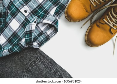 Yellow work boots, mustard color, gray jeans and green flannel shirt on a white background. Flat lay, top view. Minimal concept.
