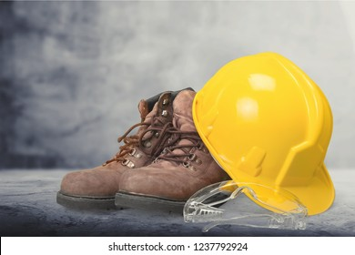 Yellow working hard hat, goggles and work boots on  background
