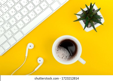 Yellow workplace with keyboard, headphones, cup of black coffee and flower pot. Online education.