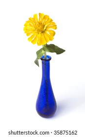 Yellow zinnia in a blue bottle vase