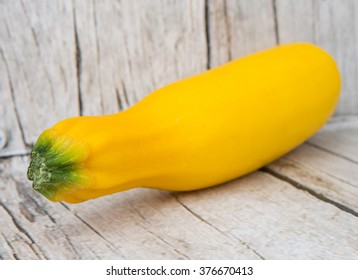 Yellow zucchini over wooden background