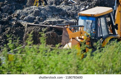 Yellowish soil digger vehicle around a construction site isolated unique photo
