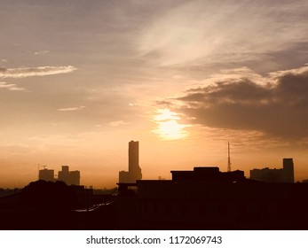A yellowish sunrise in Quezon City Philippines due to air pollution with silhouettes of buildings in the foreground.