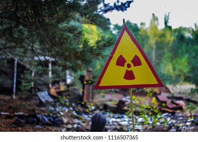 yellow-red triangular radiation sign against the background of radioactive waste warns the workers of the landfill about the danger of infection by radiation