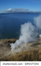 Yellowstone Lake and Hot Springs - Blue lake waters with steam rising from hot springs in foreground in Yellowstone National Park,