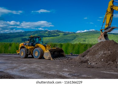 YELLOWSTONE NATIONAL PARK, WYOMING, USA - JUNE 07, 2018: Road construction equipment parked in a construction zone. Roadwork in Yellowstone National Park in gorgeous sunny day and blue sky background