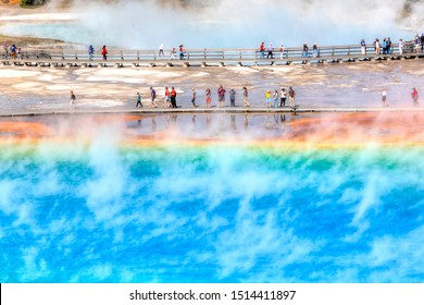YELLOWSTONE, USA - AUG 24, 2019: Tourists on the boardwalk at Grand Prismatic Spring, the largest hot spring at Yellowstone National Park.