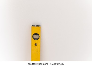 Yellowwater balance on the construction site stands in front of a white wall