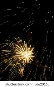 Yellow-white embers falling all around small white-hot burst of fireworks with puffs of smoke