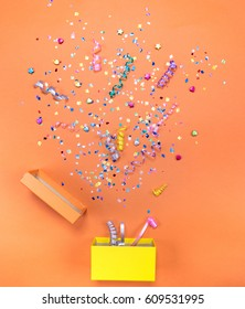 Yelow gift box with various party confetti, streamers, noisemakers and decoration on a orange background. Colorful celebration background.