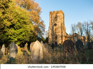 Yelvertoft, Northamptonshire / UK - November 12th 2017: All Saints church tower and clock in its overgrown graveyard with gravestones lit by evening sun.