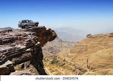 YEMEN - MARCH 13, 2010: Off-road vehicle on the edge of a steep cliff over breakaway at plateau Bokur (800m high). Extreme mountain safari is one of the main local tourist attraction in Yemen