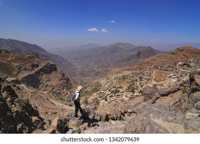 Yemen - March 14, 2010: A lonely man with backpack is standing on the edge of the cliff over a Yemen village