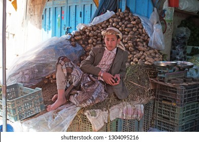 Yemen, Middle East, 05/02/2013: a boy wearing turban and dishdasha (the traditional yemeni dress) lying on a pile of potatoes in Suq al-Milh, the salt market of the old city of Sana'a