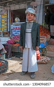 Yemen, Middle East, 05/02/2013: a child wearing dishdasha, the traditional dress, in Suq al-Milh, the salt market of Sana'a, capital of the country, the oldest continuously inhabited city in the world