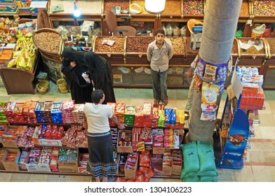 Yemen, Middle East, 05/02/2013: man and veiled women in the grocery shop of the covered market in Suq al-Milh, the salt market of Sana'a,  the oldest continuously inhabited city in the world