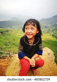 Yen Bai, Vietnam - Sep 17, 2016: Portrait of a little Hmong (Miao) minority girl sitting on a rock at a valley of yellow rice paddy field in time of harvest in Mu Cang Chai district.