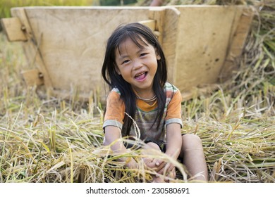 Yen Bai, Vietnam - Sep 27, 2014: Portrait of unidentified smiling Hmong child sit on paddy field waiting for her mother finish working on field