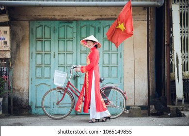 Yenbai, Vietnam - September 23 : Beautiful woman with red Ao Dai of Vietnam tradition dress standing with her bicycle at town in Mu Cang Chai on september, 2016 in Yenbai, Vietnam.
