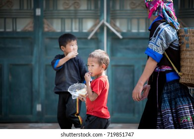 Yenbai, Vietnam - September 23 : Vietnamese woman and two of her children walking on the road to go to work at town in Mu Cang Chai on september, 2016 in Yenbai, Vietnam.