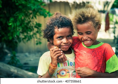 Yenbuba village, Indonesia - June 2015: Two native girls dressed in colourful clothes smile happily and hug at Yenbuba village at Mansuar Island, West Papua, Indonesia. Documentary editorial.