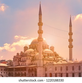 Yeni Cami Ottoman imperial mosque located in the Eminönü quarter of Istanbul, Turkey. Sunset cloudy sky in background.